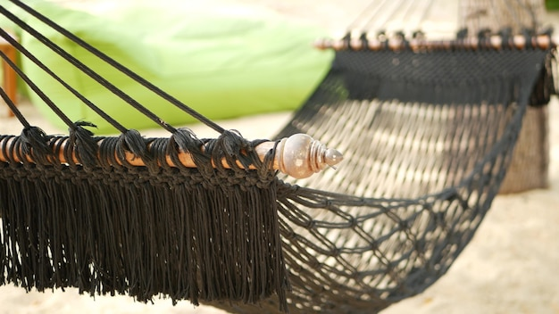 ココヤシの木の間に伸びる黒いハンモック。砂浜の楽園のビーチにフリンジ付きメッシュハンモック。