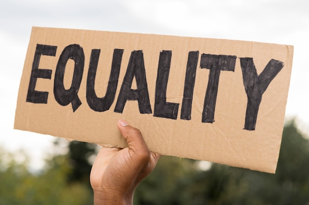 Black hand holding equality on cardboard