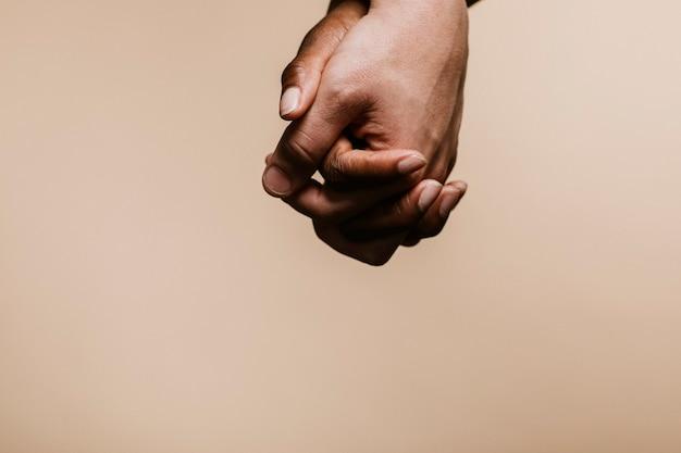 白い手を握っている黒い手