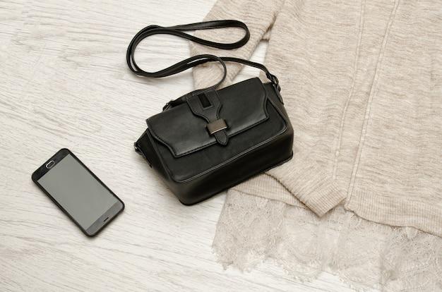 베이지 색 카디건에 검은 핸드백과 휴대 전화. 나무 배경입니다. 유행 개념, 평면도