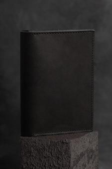 Черный кожаный кошелек ручной работы на бетонной поверхности