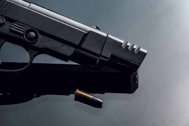 Black handgun on black background with reflection close up