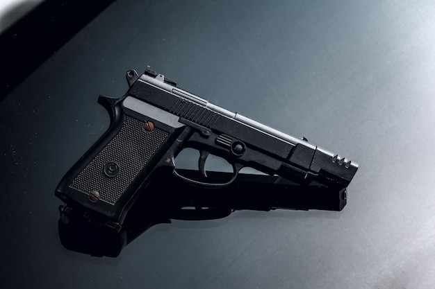 Black handgun on black  with reflection close up