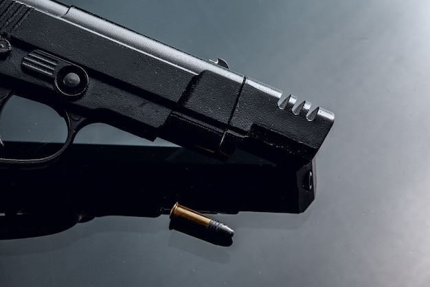 반사와 검은 배경에 검은 권총을 닫습니다.
