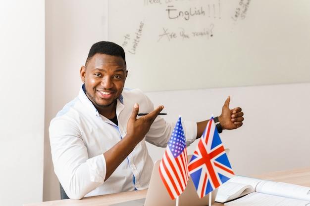 黒人のハンサムな男は微笑み、顔をゆがめ、社会的距離に応じてオンライン作業に彼のラップトップを使用します