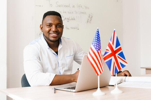 黒人のハンサムな男は、社会的距離に応じてオンライン作業に彼のラップトップを使用しています