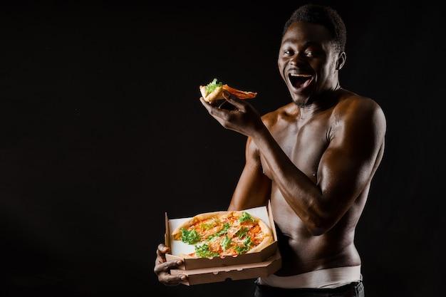 흑인 잘생긴 벌거벗은 남자가 피자를 먹는다. 집에 머무는 사람들을 위한 안전한 음식 배달. 섹시한 아프리카 남자가 손에 피자 2조각을 보여줍니다.