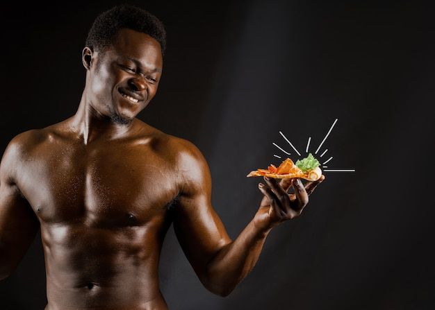 Black handsome naked man eats a pizza with cheese boards