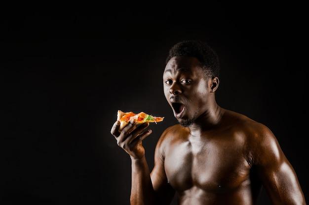 Black handsome naked man eats a pizza
