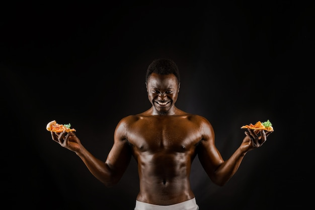 Black handsome naked man with a pizza