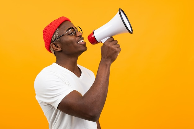 Black handsome smiling american man in white t-shirt speaks news through a megaphone on isolated orange background