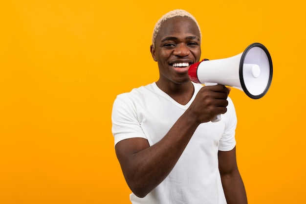 Black handsome smiling american man in white t-shirt speaks news through a megaphone on isolated orange