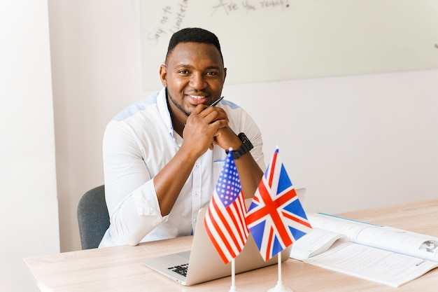 黒人のハンサムな翻訳者は、社会的距離に応じてオンライン作業に彼のラップトップを使用しています