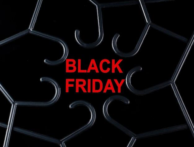 검정색 옷걸이와 검정색 배경에 black friday라는 텍스트가 있습니다. 할인. 시즌 세일.