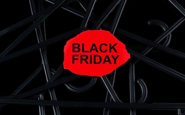 검정색 옷걸이와 검정색 배경에 있는 토르 종이에 black friday라는 텍스트가 있습니다. 할인. 시즌 세일.