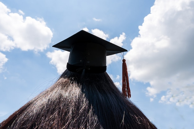 Black hat of the graduates floating in the sky.