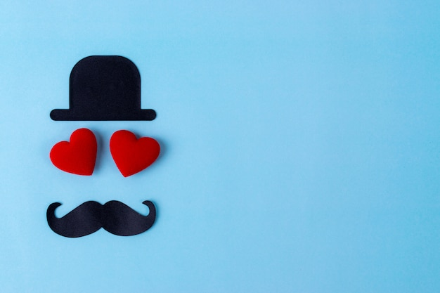 Black hat, mustache and two red heart with pastel blue background.