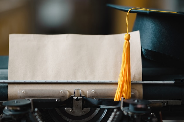 A black hat with a yellow tassel of a graduate is placed on a typewriter.