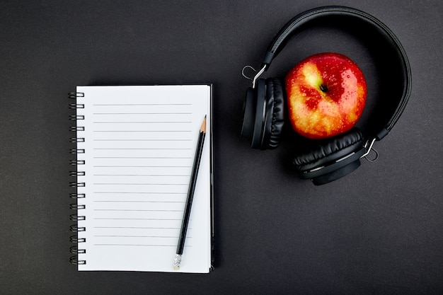 Черные наушники и яблоко