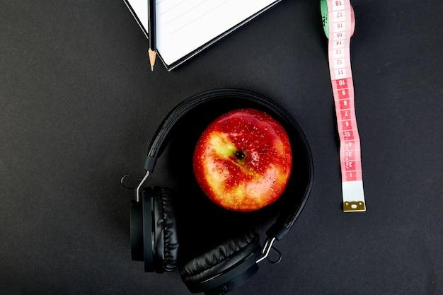 黒のヘッドフォンとリンゴ