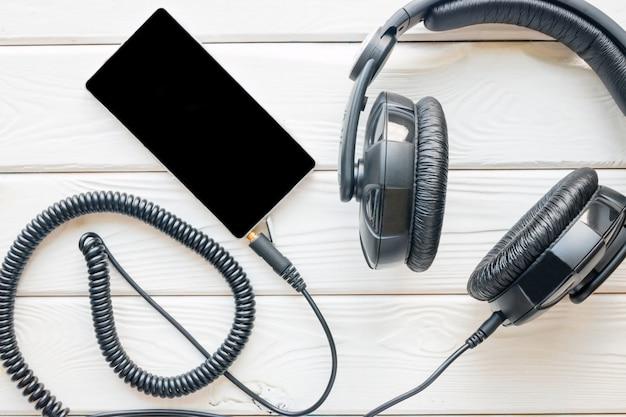 Черные наушники и смартфон на белом фоне
