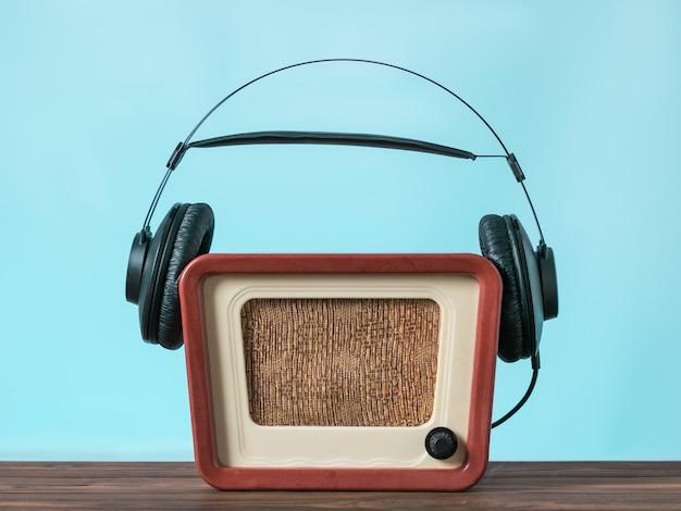 검은색 헤드폰은 파란색 배경의 나무 테이블에 있는 빈티지 모니터에 착용됩니다. 사운드 및 비디오 재생 기술.
