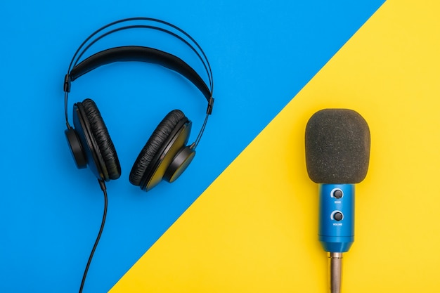 Black headphones and blue microphone on light yellow and blue.