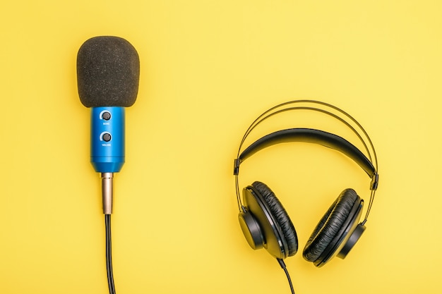 Black headphones and blue microphone on light yellow.