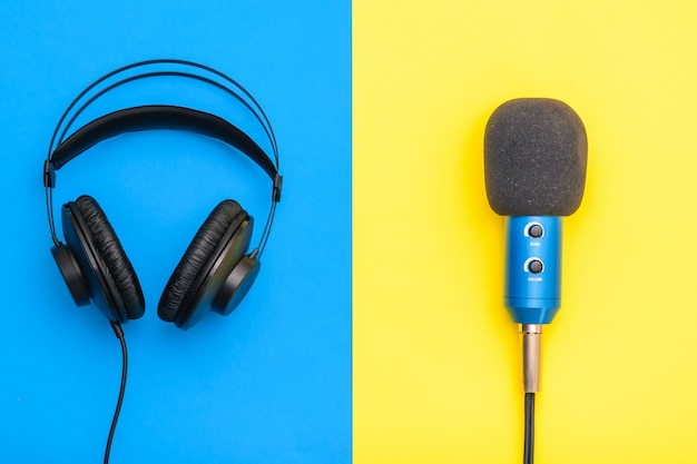 Black headphones and blue microphone on yellow and blue