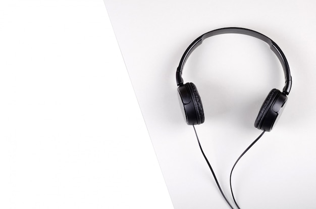 Black headphones composition on gray background. flat lay.
