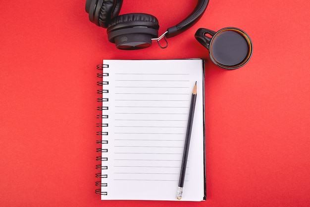 Black headphones and cup of coffee with notebook, note on red background. flat lay. top view. copy space.