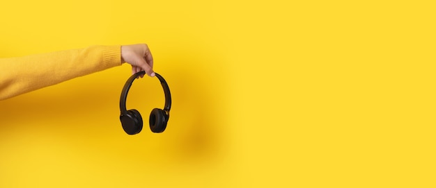 Black headphones in hand on yellow background, panoramic image