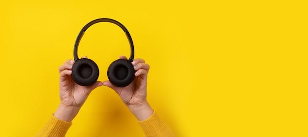Black headphones in hand on yellow background