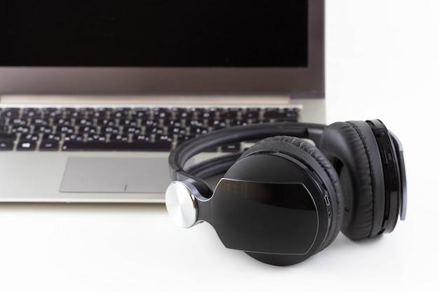 Черные наушники лежат возле компьютера