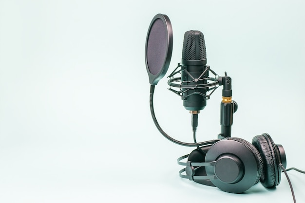 Black headphones and microphone with wires on a light blue surface. sound recording equipment.