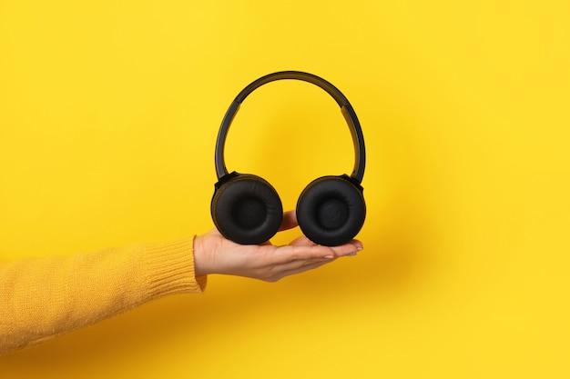 노란색 배경 위에 손에 검은 헤드폰