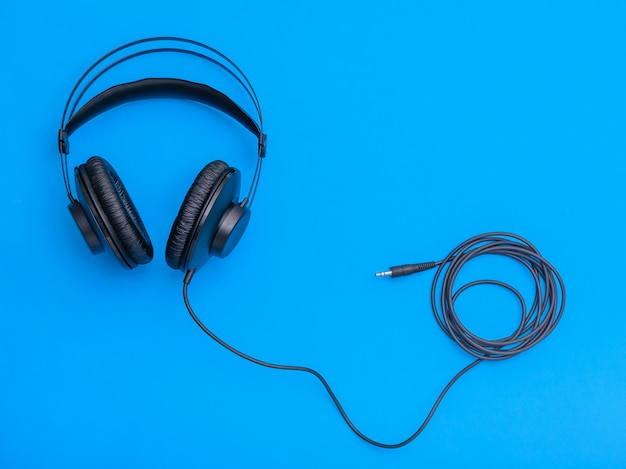 Black headphones with coiled cord on blue background.