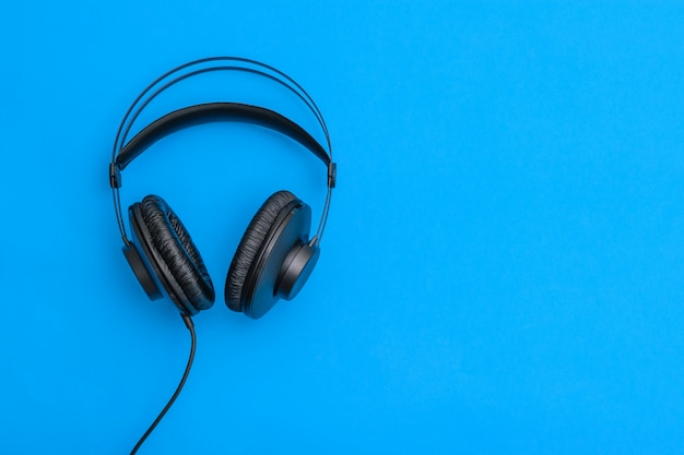 Black headphones with coiled cord on light blue