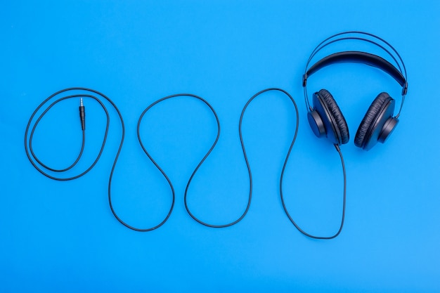 Black headphones with cord in shape of wave on a blue background. accessory for listening to music and communication.