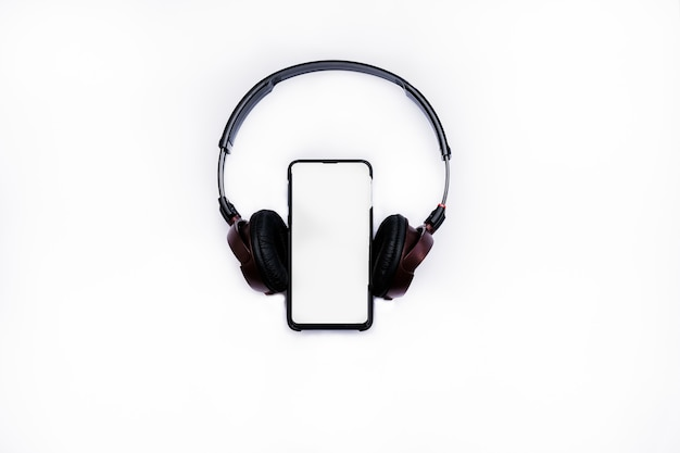 Black headphones with the phone isolated on white background.