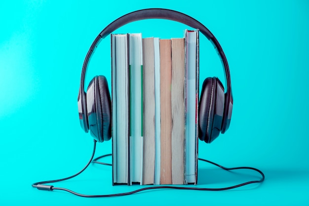 Black headphones with a stack of books on a blue background.