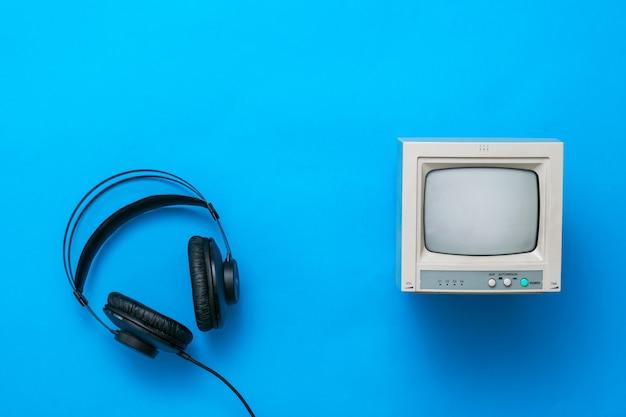파란색 배경에 와이어와 작은 복고풍 모니터가 있는 검은색 헤드폰. 사운드 및 비디오 재생 기술.