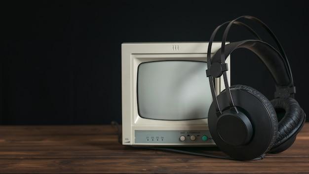검은색 바탕에 나무 테이블에 철사와 복고풍 모니터가 있는 검은색 헤드폰. 사운드 및 비디오 재생 기술.