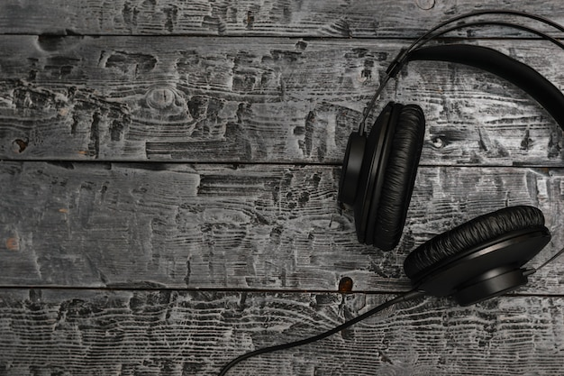 Black headphones with wire on black wooden table.