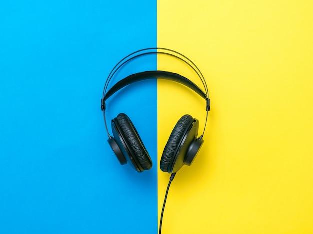 黄色と青の背景にワイヤーと黒のヘッドフォン。モバイルオーディオ再生機器。