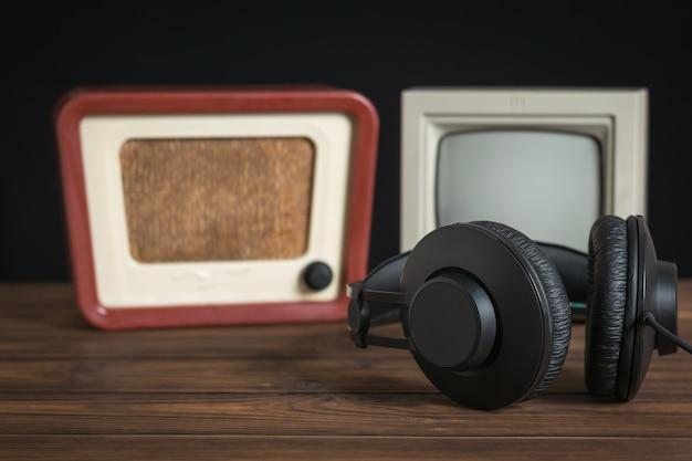 Черные наушники с проводами на фоне антикварного монитора и радио. набор старинного радиооборудования.