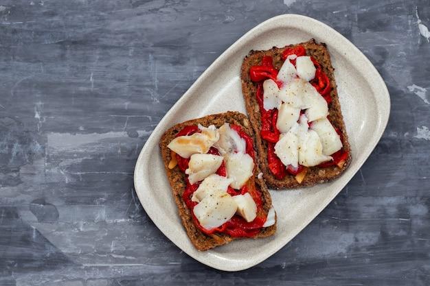 Черный здоровый хлеб с треской и красным перцем на блюде