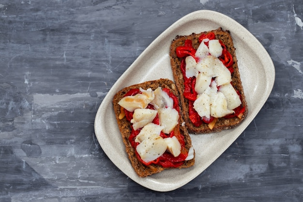Black healthy bread with cod fish and red pepper on dish