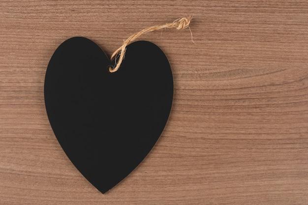 Черное сердце на деревянных фоне.