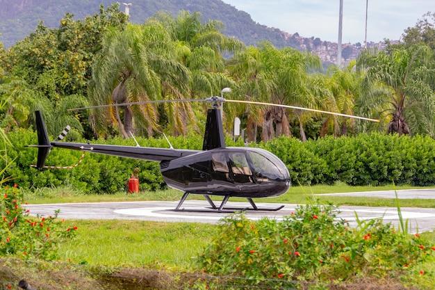 Черный вертолет модели r44 ворон остановится на вертолетной площадке лагуны родриго де фрейтас в рио-де-жанейро.